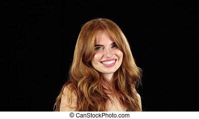 Redhaired girl flirting. Black background. Slow motion -...