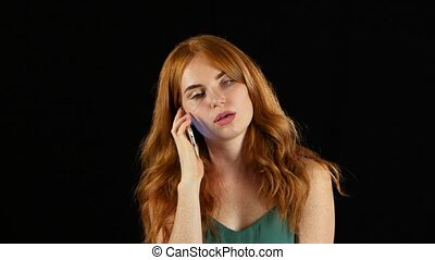Redhaired girl talking on the phone. Black background -...