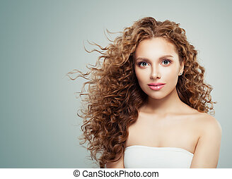 Redhead beauty. Young female face, woman with long healthy wavy hair