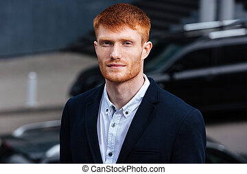 Redhead businessman looking at camera outdoors