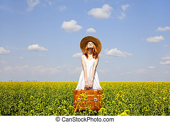 Redhead enchantress with suitcase at spring rapeseed field.