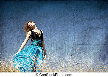 Redhead girl at windy field. Photo in old color image style.