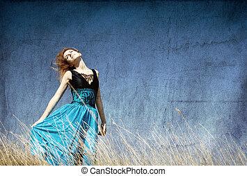 Redhead girl at windy field.