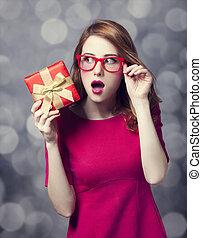 Redhead girl in dress with present box. Bokeh.