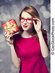 Redhead girl in dress with present box. Bokeh.