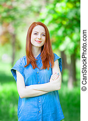 Redhead girl in the park in spring time.