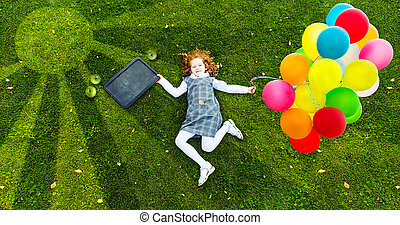 Redhead girl lying on the green grass in park, high top view.