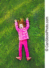 Redhead girl lying on the green grass in park.
