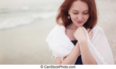 redhead girl on the seashore laughs
