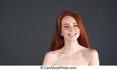 Redhead girl smiling closeup portrait. Young woman looking...