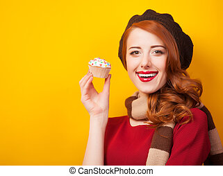 Redhead girl with cake on yellow background.