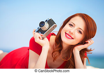 Redhead girl with camera on the beach