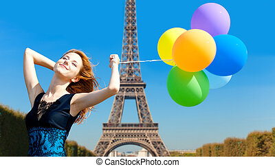 Redhead girl with colour balloons on parisian Eiffel tower...