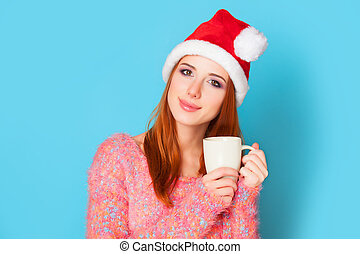 Redhead girl with cup on blue background.