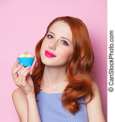 Redhead girl with cupcake in pink background.