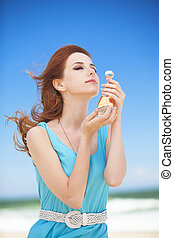 Redhead girl with perfume on the beach