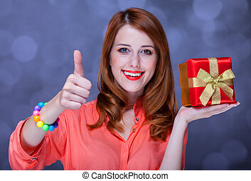 Redhead girl with present box. Bokeh.