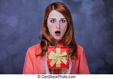 Redhead girl with present box. Bokeh.