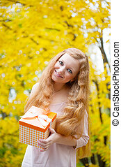Redhead girl with present box in autumn park