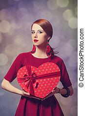 Redhead girl with shape heart box.