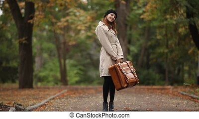 Redhead girl with suitcase at outdo