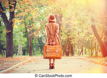 Redhead girl with suitcase in the autumn park.