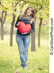 Redhead girl with toy heart at autumn park.