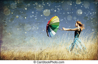 Redhead girl with umbrella at windy grass meadow. Photo in...