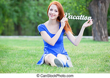 Redhead girl with word Vacation in the park.