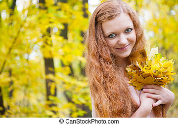 Redhead girl with yellow autumn leaves