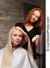 redhead hairdresser applying mousse on client's hair and smiling. Female hairdresser works on woman hair in salon