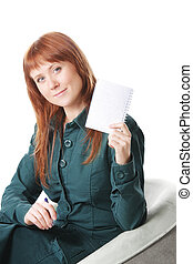 Redhead in chair showing notepad