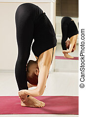 Redhead in standing forward bend yoga pose