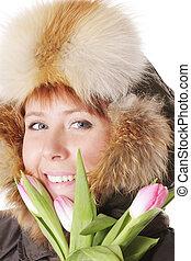 Redhead in warm hood behind tulips