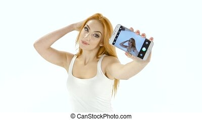 Redhead model girl doing selfie on your smartphone. White studio