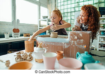 redhead mother and her child daughter moulding with clay on pottery wheel