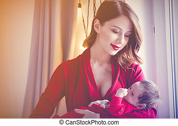 Redhead mother with new born child in red