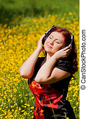 redhead pretty girl with headphones listening to music in nature in a field of flowers