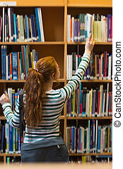 Redhead student taking book from shelf in library at the...