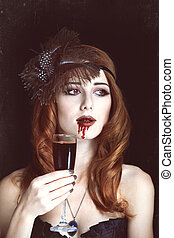 Redhead vampire woman with glass of blood. Photo in vintage...