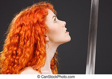 redhead warrior - lovely redhead with medieval sword over...