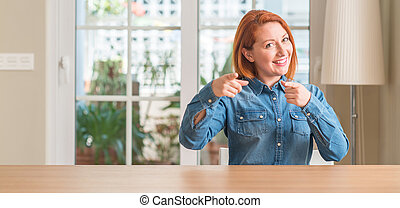 Redhead woman at home pointing fingers to camera with happy...