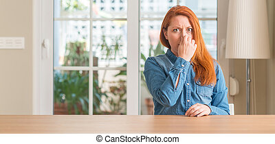 Redhead woman at home smelling something stinky and disgusting, intolerable smell, holding breath with fingers on nose. Bad smells concept.