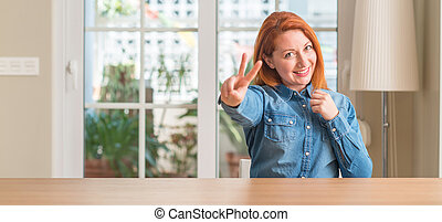 Redhead woman at home smiling looking to the camera showing fingers doing victory sign. Number two.