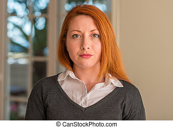 Redhead woman at home with a confident expression on smart face thinking serious
