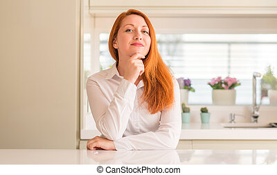 Redhead woman at kitchen looking confident at the camera with smile with crossed arms and hand raised on chin. Thinking positive.