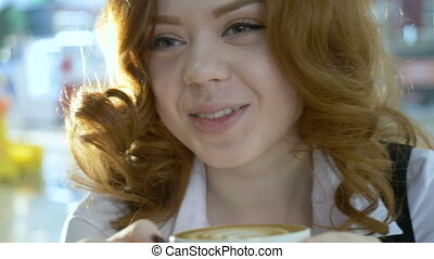 Redhead woman drinking cappuccino in cafe. - Young...