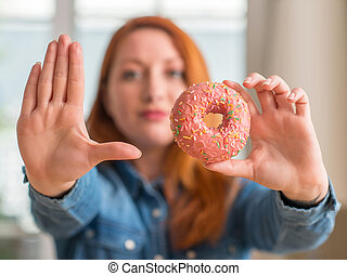 Redhead woman holding donut at home with open hand doing ...