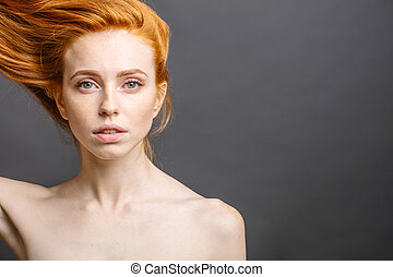 redhead woman holding her healthy and shiny hair, studio grey