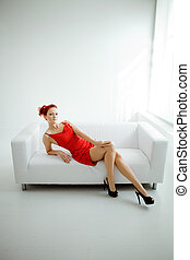 Redhead woman in a red dress on white couch